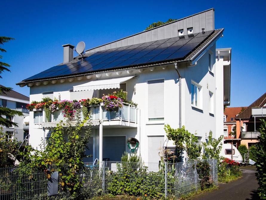 Zweifamilienhaus mit abgeknickten gegenläufigen Pultdächern und überdachter Terasse.
