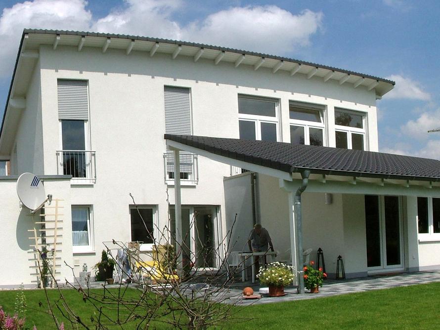 Gestaffeltes Zweifamilienhaus mit gegenläufigen Pultdächern und überdachter Terasse.